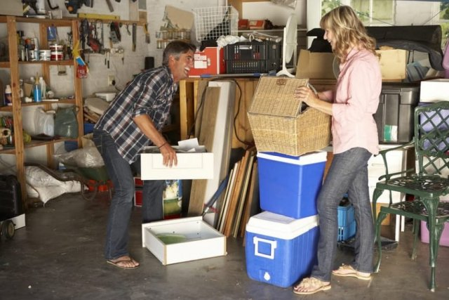 couple moving items in messy garage